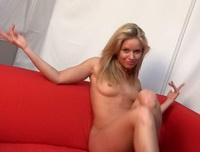 Savannnah is completely naked on a red couch