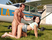 A guy and a young girl are standing next to a small airplane. She gives him a blow job and then he fucks her up her ass and in her pussy, making her moan with pleasure until he comes.
