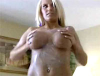 Amazing busty blonde puts cream on her body