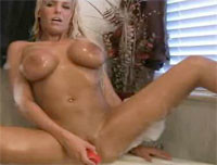 Busty blonde Ember Reigns toying her pussy in tub
